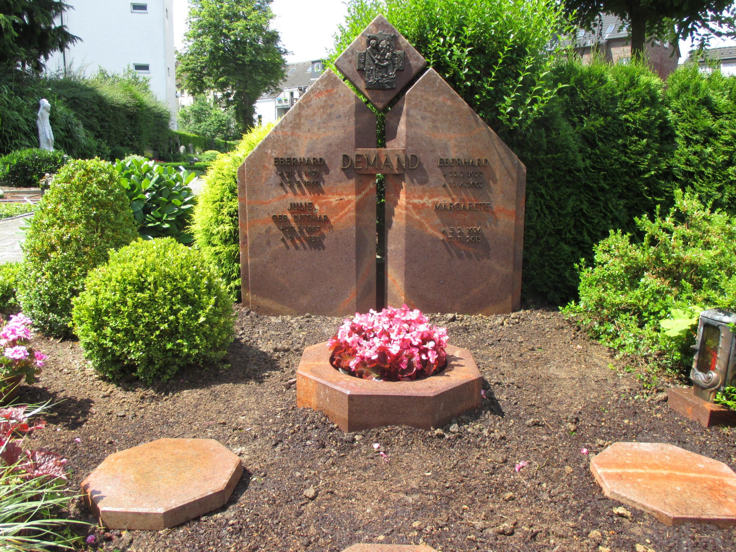 Grabanlage Demand. Rochlitzer Porphyr mit Bronzeinschrift, Trittplatten und Pflanzring.